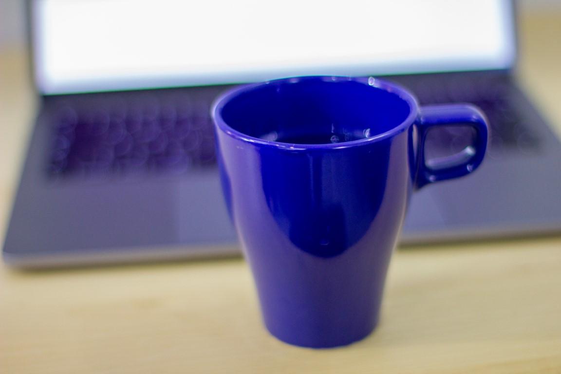 Bildet viser en blå kopp foran en Apple Mac bærbar PC og er ment å visualisere arbeid på nettet for å komme høyt opp i Google på nettstedet OMACO AS